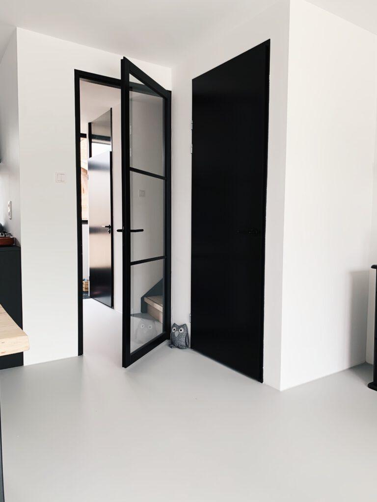 zwarte deuren en kozijnen in de hal en woonkamer