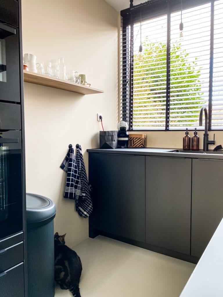 aanzicht van de linker kant van de zwarte ikea keuken, prullenbak, vaatwasser en serviesplank