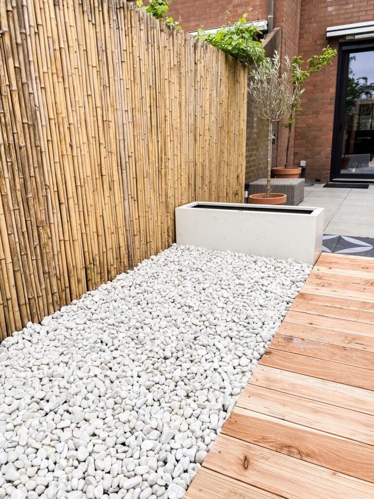 sfeerbeeld tropische tuin met grind, vlonderpad en bamboe schermen