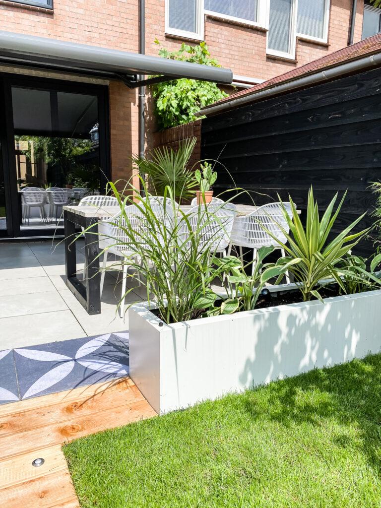 tropische tuin inspiratie planten met witte plantenbakken en eethoek aanzicht.